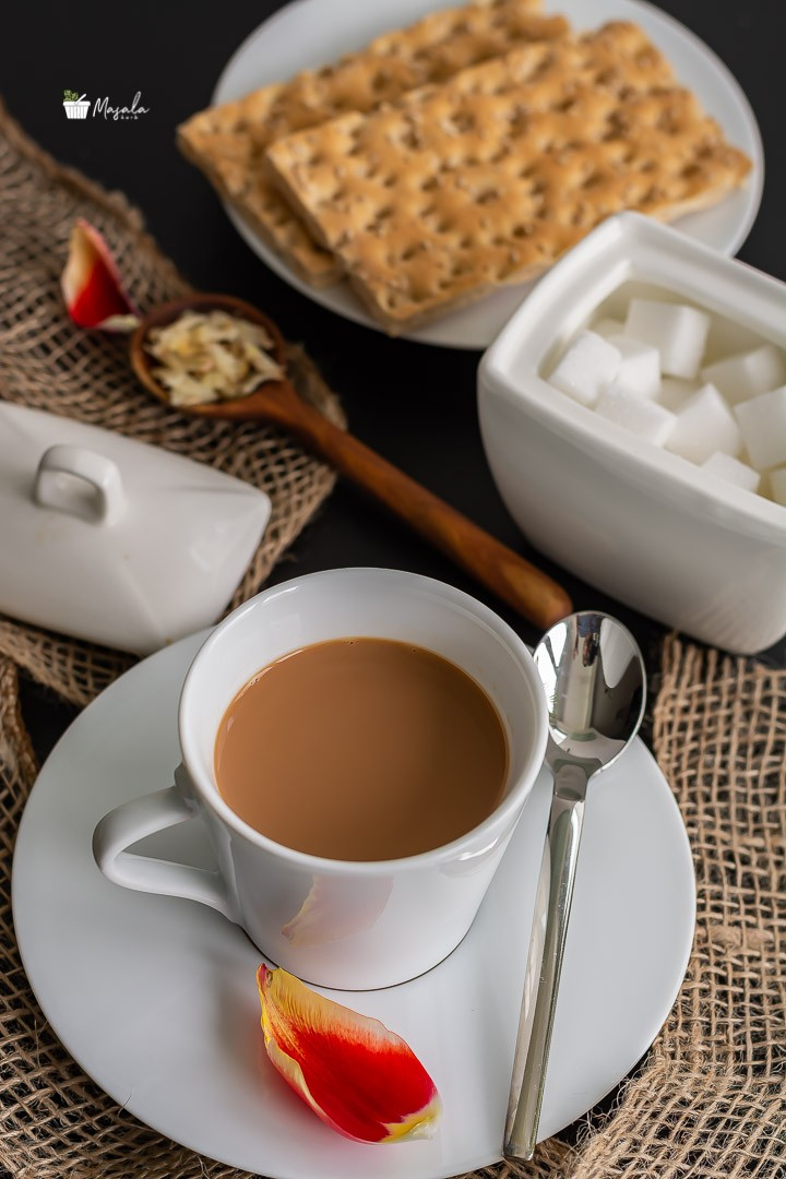 Adrak Wali Chai served in a white cup & saucer.