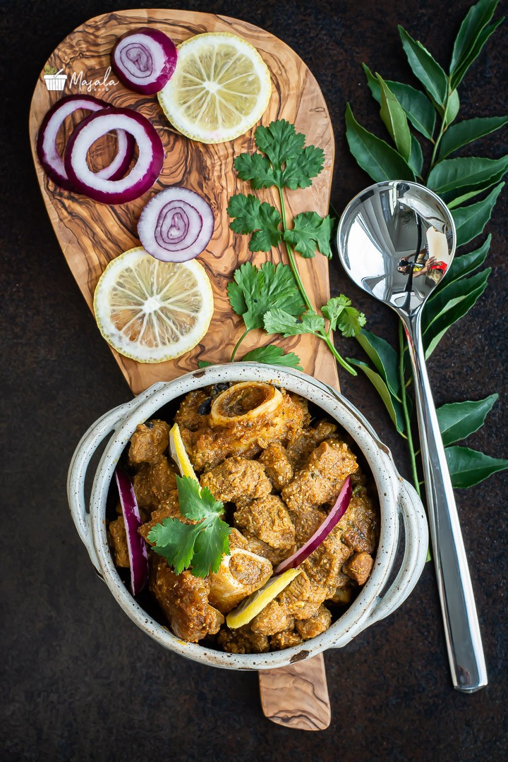 Mutton curry served with lemon wedges & onion slices.