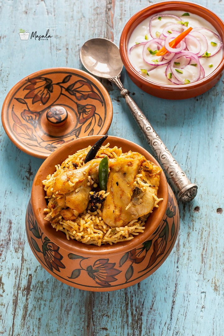 Chicken Biryani served in a clay pot with raita on the side