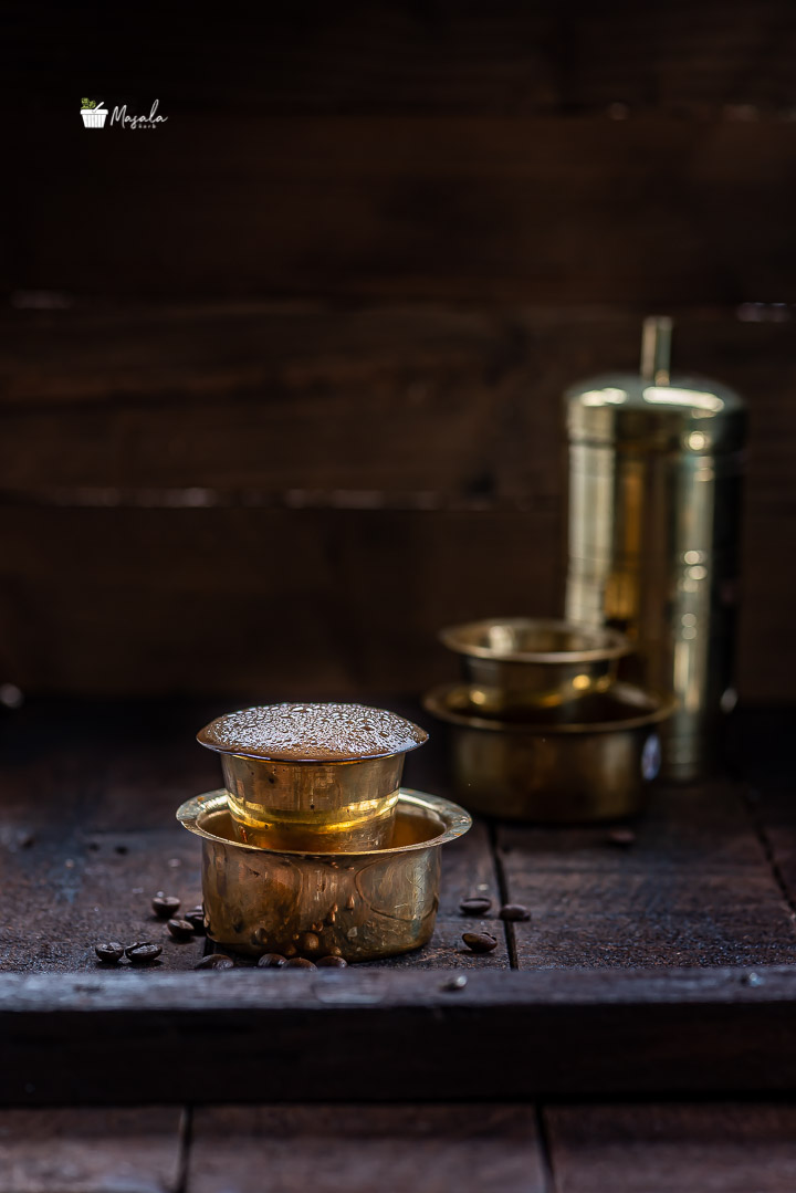 Filter coffee served in a brass dabarah and tumbler and the brass filter apparatus in frame.
