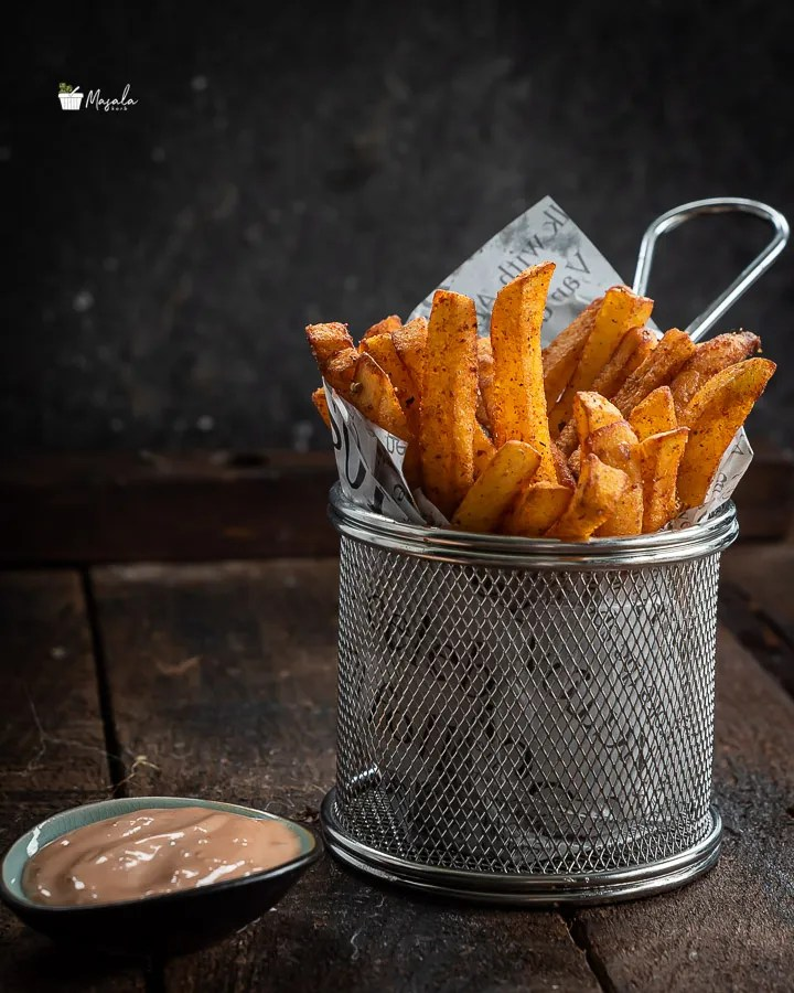 Crispy Masala French Fries served in a mesh tin.