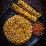 Gujarati Methi Thepla served on a black plate with mango pickle