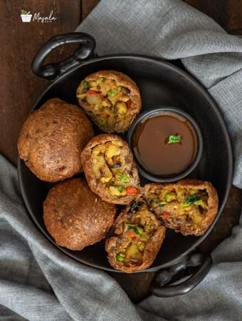 Potato Bread Rolls Recipe Indian - Bread Bonda Recipe served on a black plate