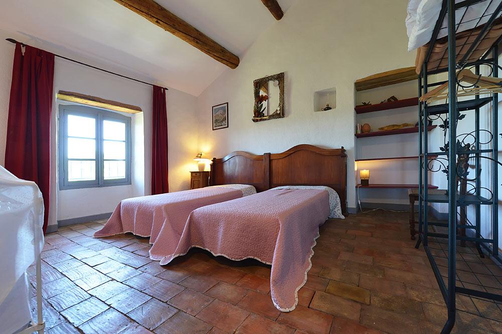La chambre avec parfeuilles, étagères et deux lits simples au Tamaris au Mas de la Baillyde, gîtes de charme en Cévennes