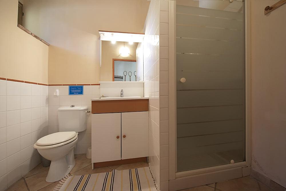 La salle de bain avec WC, lavabo et douche aux Treilles au Mas de la Baillyde, gîtes de charme en Cévennes