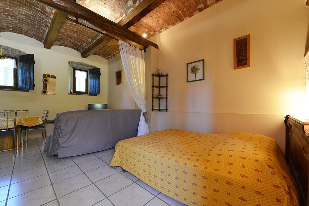 Le lit double dans le studio Romarin avec plafond voûté au Mas de la Baillyde, gîtes de charme en Cévennes