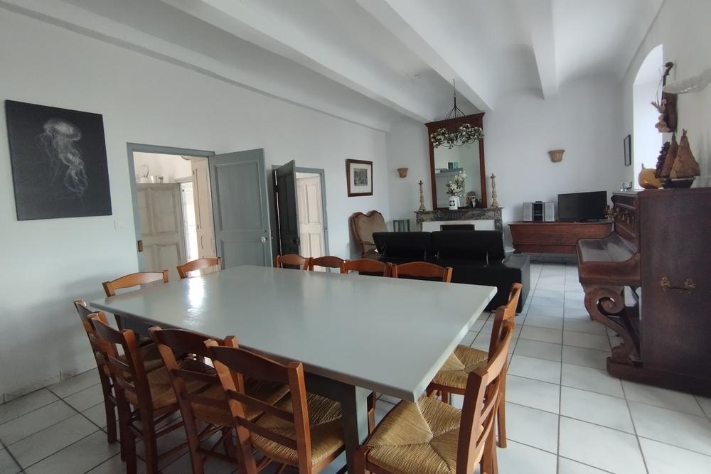 Le salon avec piano et grande table à manger au Tamaris au Mas de la Baillyde, gîtes de charme en Cévennes