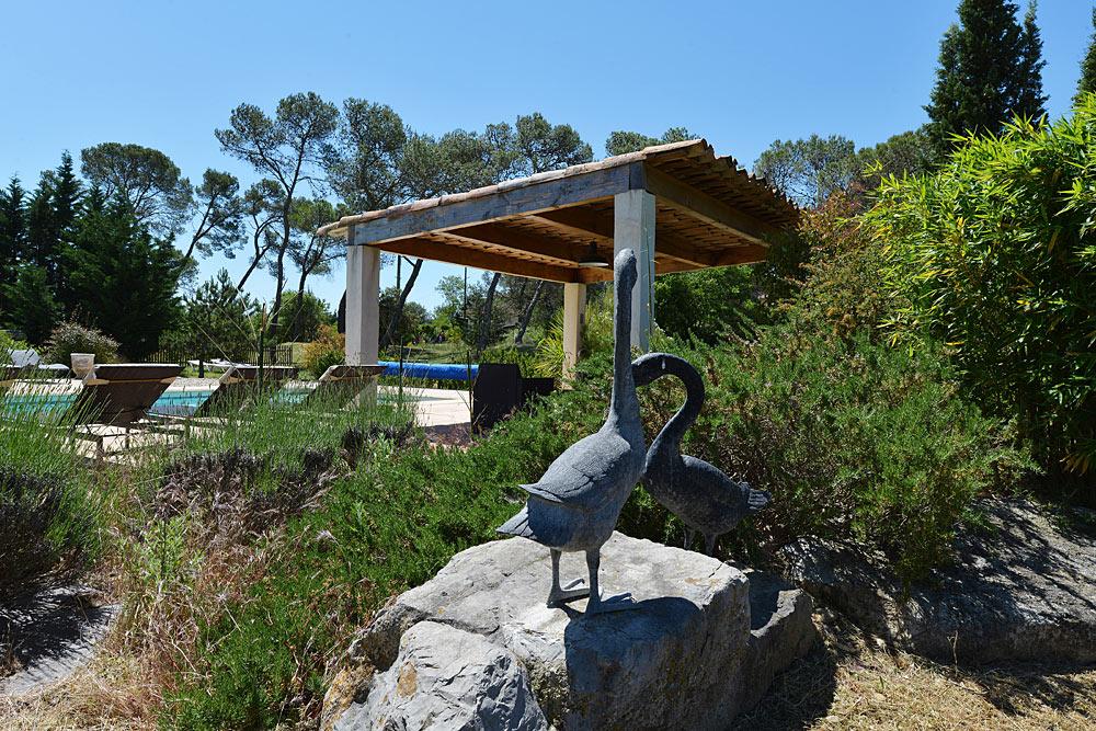 Statues et structure ombragé au bord de la piscine dans les jardins au Mas de la Baillyde, gîtes de charme en Cévennes