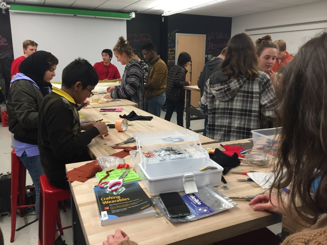 A group of students work at tables to create wearable tech. Some students are seated, others are standing. There are containers and supplies all over the tables, and a book on how to create wearable tech.