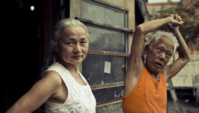 Noriko Shinohara (l.) looks in the camera as her husband Ushio stretches. From Zachary Heinzerling's CUTIE AND THE BOXER, a documentary about the 40-year marriage of artists Ushio and Noriko Shinohara. Photo credit: Erik Jonsso