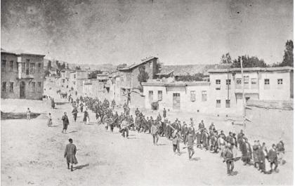 Civili armeni in marcia forzata verso il campo di prigionia di Mezireh, sorvegliati da soldati turchi armati. Kharpert, Impero Ottomano, aprile 1915 - American Red Cross, pubblico dominio