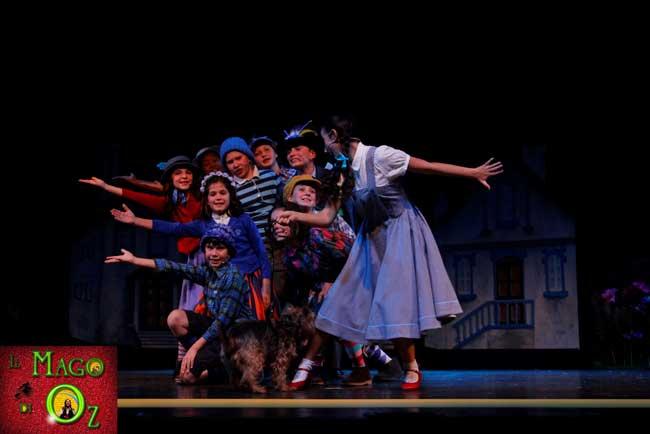 Una scena del musical Il Mago di Oz: i Mastichini indicano a Dorothy il Dorato Sentier che la condurrà ad Oz, dal celebre Mago