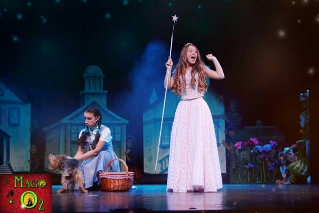 """Una scena del musical Il Mago di Oz: i Mastichini ridono perchè Dorothy dice che """"le streghe sono brutte, con i porri sul naso e sul mento"""" ma non sa che anche la bella Glinda è una Strega, la Strega buona del Nord"""