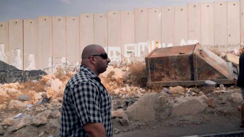 "L'uomo che rubò Bansky: Walid ""The Beast"" davanti al muro fra Palestina e Israele -Photo courtesy of Nexo Digital"