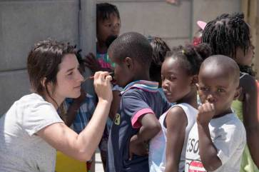 Volunteer helps with Face painting fun at Masi Educare - Masiphumlele ECD