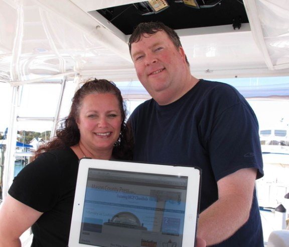 Rob and Becky Alway, owners of MCP, hold up their iPad while on vacation in Key West.