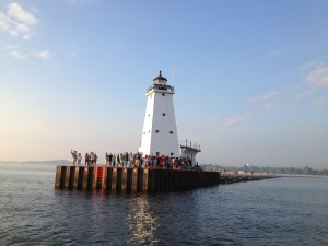 Dozens of people line the Ludington north pier lighthouse on July 3, 2013 to watch the Badger leave port.