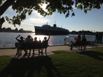 A family waves at the Badger as it prepares to dock in Ludington. The ship brings millions of dollars into the economy of Mason County.