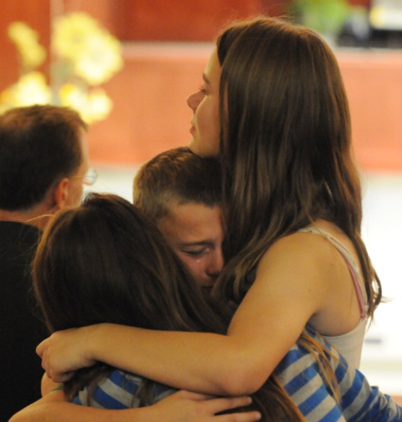 Francis Knizacky comforts her brother, Daniel and another classmate.