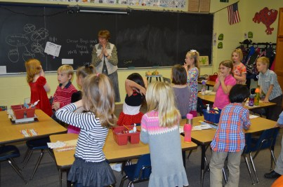 First grade students pray in an LAC classroom