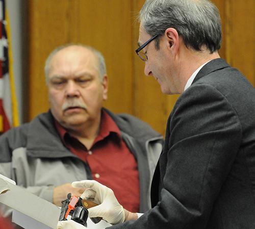 Prosecutor Paul Spaniola shows John Knysz the murder weapon. John bought the gun in 1972.