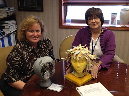 Left, Conny Bax and Beth Ann Morsman show off two of the Life Blooms foam wig heads designed by different local and craft industry artists. The heads will be auctioned off at the Life Blooms event, 5-9 p.m., Saturday at Lincoln Hills Country Club. The event is sponsored by Floracraft.
