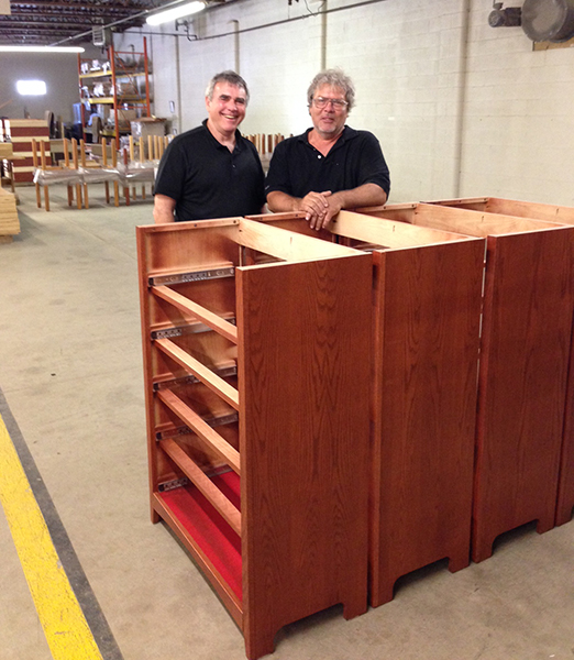 Left, Brill President David Field and Operations Manager Paul Lange stand in front of some dressers being manufactured for college dorm rooms by The Brill Company.