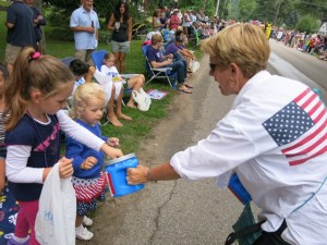 Amy LaBarge of Pentwater collects funds from one of the many young Homecoming Parade spectators who contributed.