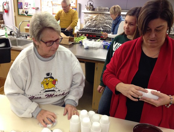 Joyce Usiak, left, along with Julia and Megan Maltbie, prepare items in the kitchen.