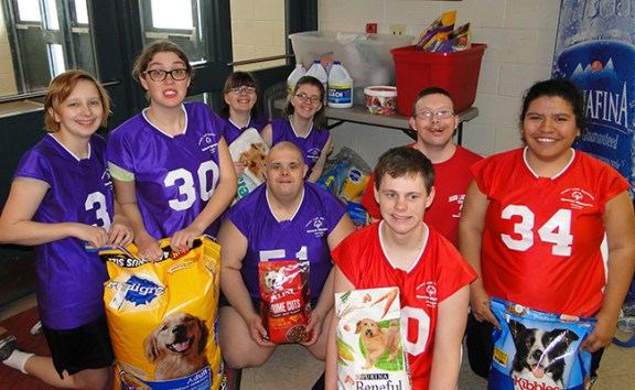 Members of Area 24 Special Olympics hold some of the items to be donated to the Mason County Animal Shelter.