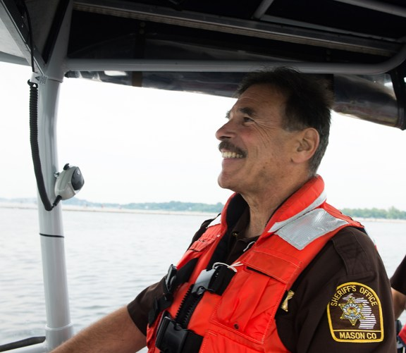 Lou Mantho smiles as he drives the sheriff's office's Boston Whaler.