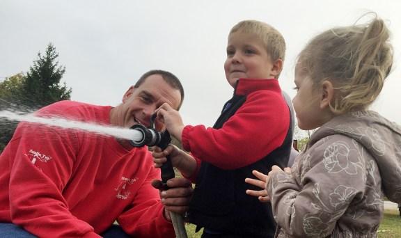 Capt. Matt Bryant helps kids spray water.