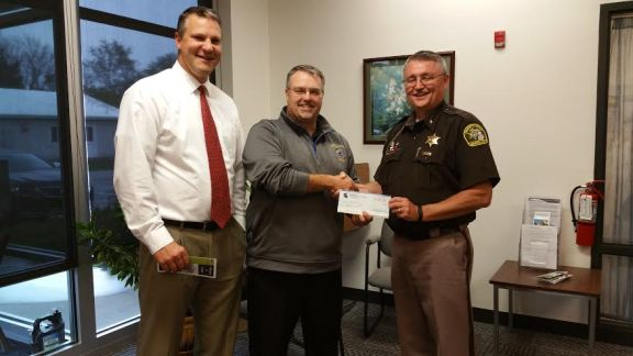 Sheriff Kim Cole, right, receives a check from Tim Genson, center, and Superintendent Jeff Mount.