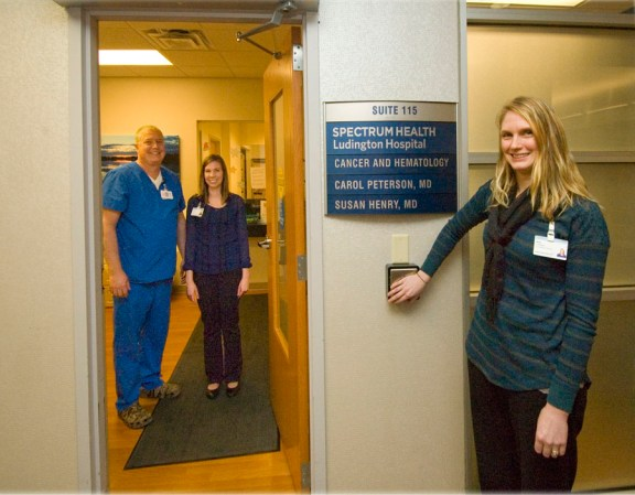 Amy Lindenau, an active member of the TEAM employee group who suggested the idea, operates the new automatic door opener to Spectrum Health Ludington Hospital's Cancer & Hematology treatment facility. The opening door reveals Brian Buter, co-chair of TEAM, and Caitlyn Outwater, Cancer & Hematology receptionist, who can also open the door from her desk so patients can easily leave after treatment.