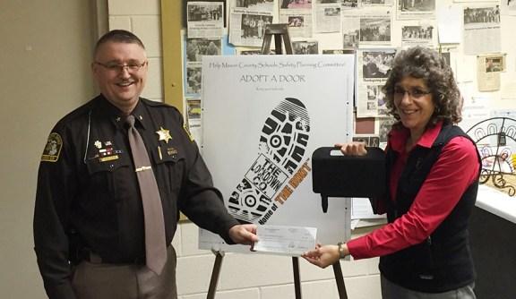 Sheriff Kim Cole, left, receives a check from Scottville Optimist President Nancy Sanford.