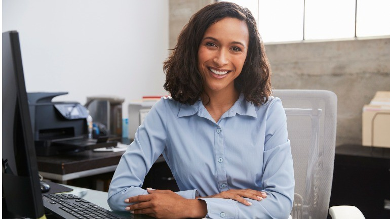 young female professional at desk smiling to camera picture id1011793090