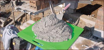 Mojster zidar je iz peska, vode, apna in cementa zmešal malto, iz katere bo zgradil hišo.