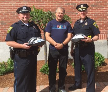 Attorney David W. White delivered helmets to Norwood Police Chief William G. Brooks III (right) and Officer Paul Murphy (left).