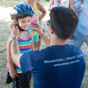 Attorney Reza Breakstone fits a helmet at the Dedham Bike Rodeo. Breakstone, White & Gluck donated 120 bike helmets to children at the Dedham Bike Rodeo. This was our fourth year participating.