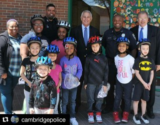 Attorney Ron Gluck and Attorney David White join the Cambridge Police and students at the Cambridgeport School. Breakstone, White & Gluck donated 140 bicycle helmets for the Cambridge Police to distribute through its first-ever helmet voucher program.