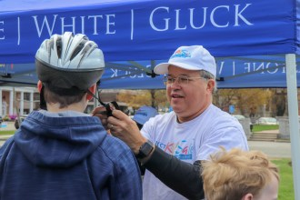 Attorney David W. White fitting helmets at Framingham Earth Day 2019. Part of Breakstone, White & Gluck's Project KidSafe campaign to prevent head injuries.