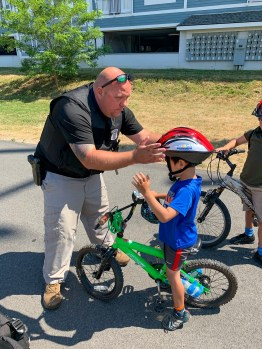 Everett Police officer fitting a free helmet for a young child. Helmet donated by Breakstone, White & Gluck's Project KidSafe campaign.