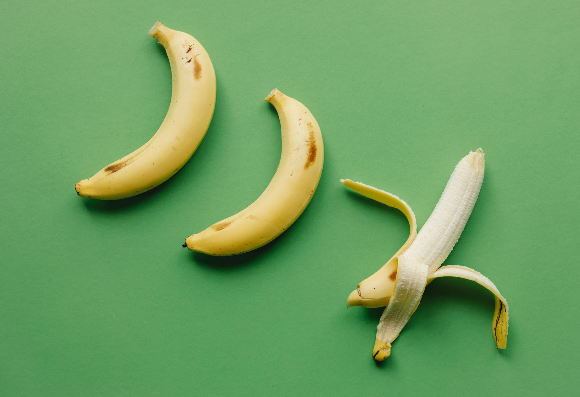 ripe bananas on green surface