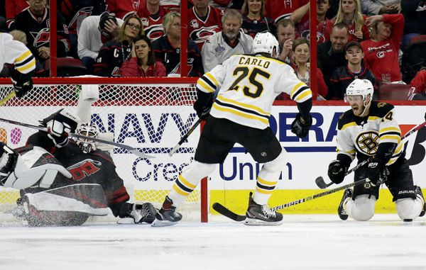 Boston Bruins' Chris Wagner (14) and Brandon Carlo (25) celebrate Wagner's goal against Carolina Hurricanes goalie Curtis McElhinney during the second period in Game 3 of the NHL hockey Stanley Cup Eastern Conference final series in Raleigh, N.C., Tuesday, May 14, 2019. (AP Photo/Gerry Broome)