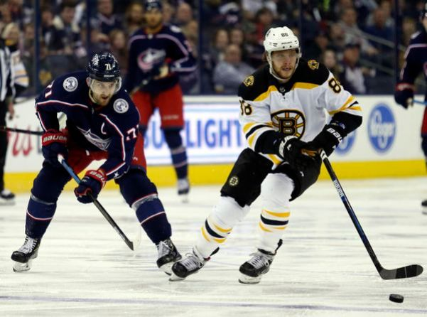 Boston Bruins forward David Pastrnak, right, of the Czech Republic, controls the puck against Columbus Blue Jackets forward Nick Foligno during an NHL hockey game in Columbus, Ohio, Tuesday, April 2, 2019. The Bruins won 6-2. (AP Photo/Paul Vernon)