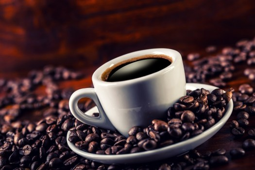 Cup of black coffee and spilled coffee beans. Coffee break ** Note: Shallow depth of field