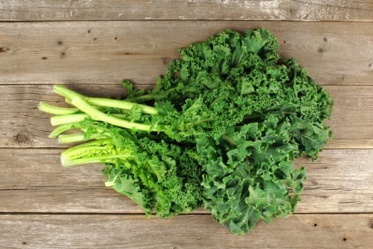 Bunch of fresh kale over a wooden background. Overhead view.