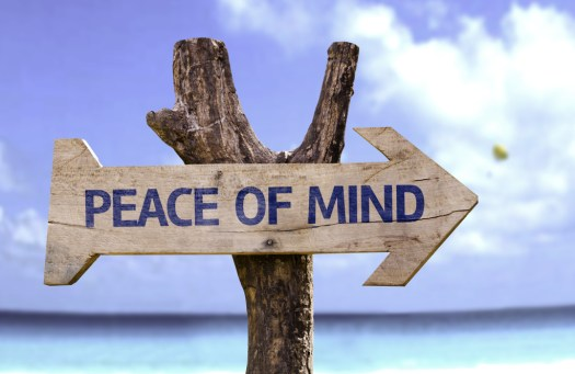 Peace of Mind wooden sign with a beach on background