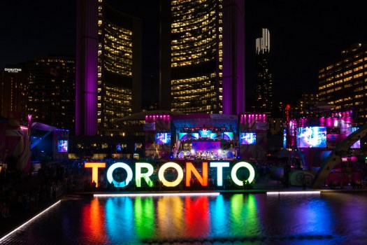 TORONTO,CANADA-JULY 20,2015: Toronto Pan American Games 2015 ambience: Nathan Phillips Square during Panamania the cultural festival that goes along the games. Beautiful Toronto sign and the New City Hall in the background