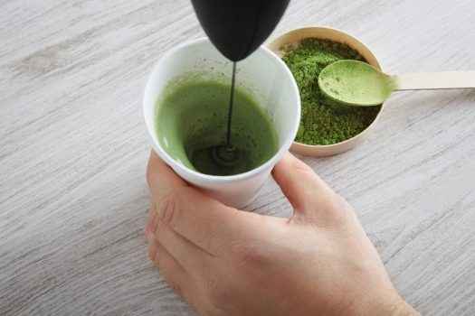 Top view take away white paper glass and premium organic japan matcha tea on wooden table ready for modern way latte preparation. Presentation fourth step. Froater milk with electric device and green powder to foam pasta.